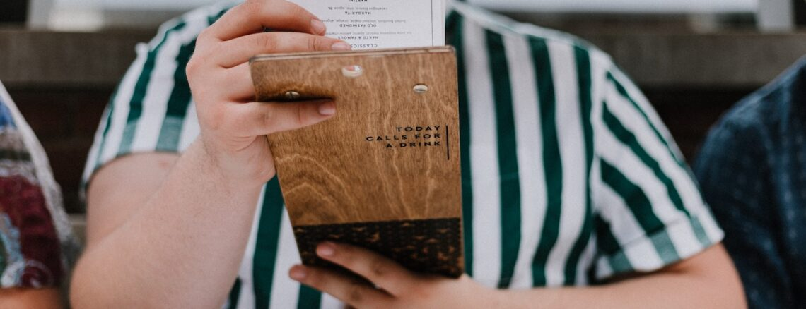 woman in a green and white striped shirt reading a restaurant menu
