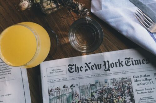 Table with newspapers, restaurant menus, and juice