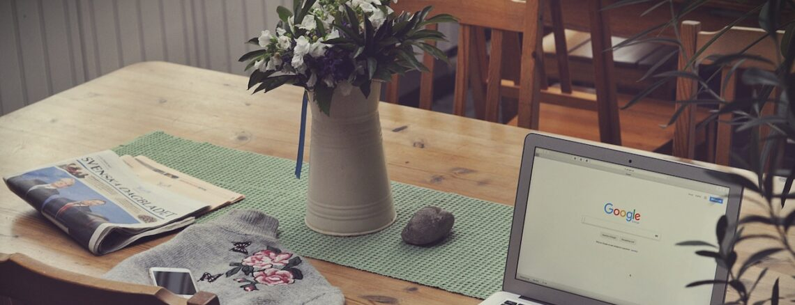 work from home setup with laptop and flowers on a wooden dining room table