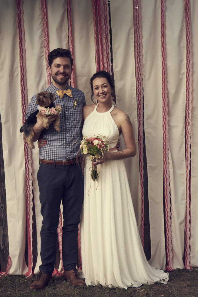 Bride and groom with their tiny dog.