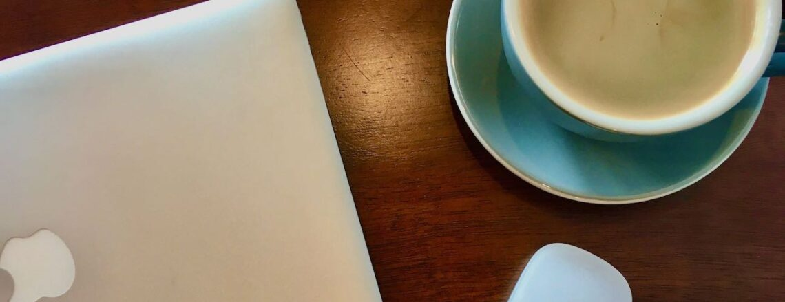laptop on a wood table with coffee cup - turn restaurant into a coworking space