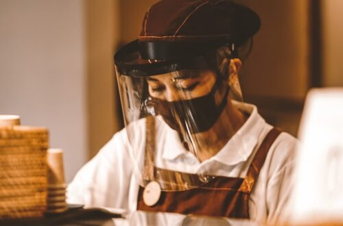 woman working at a coffee shop in face mask and shield