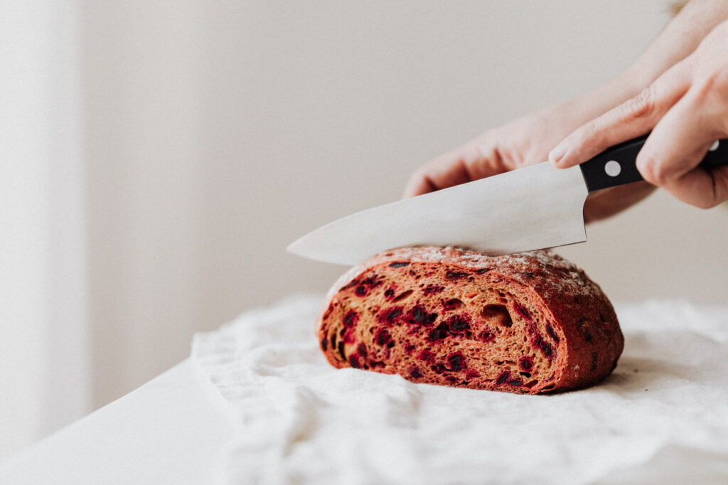 Loaf of bread on a white tea towel being sliced