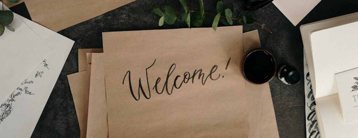 """""""Welcome"""" painted in black script on butcher paper"""
