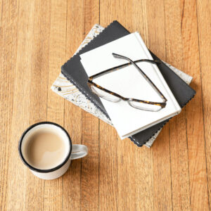 White notebook with black glasses and mug of coffee