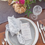 Menu on a grey plate with fall flowers on a brown table