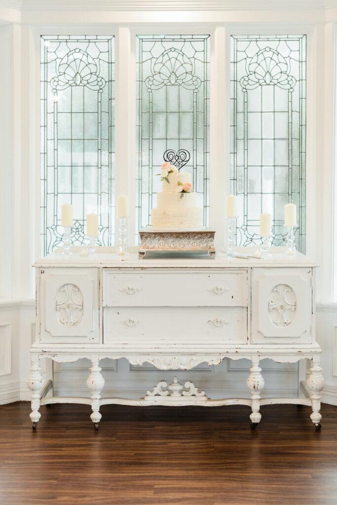White table with white wedding cake on top