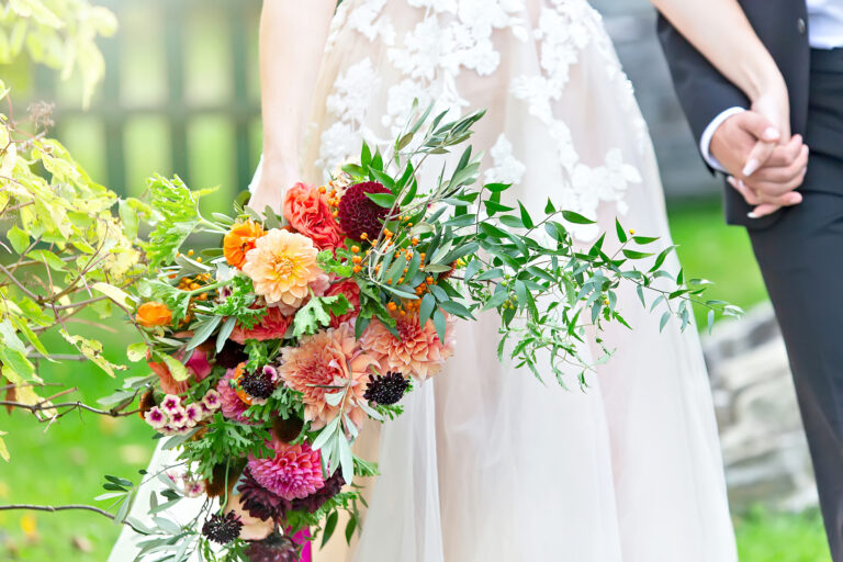 Bride and groom hand in hand with a bright floral bouquet