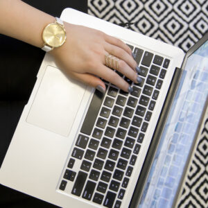 Hand with a gold watch on a laptop to symbolize blog writing service