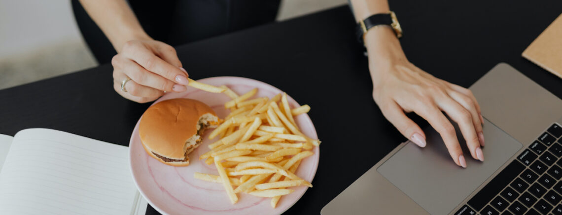 Woman working on a laptop with a cheeseburger and french fries