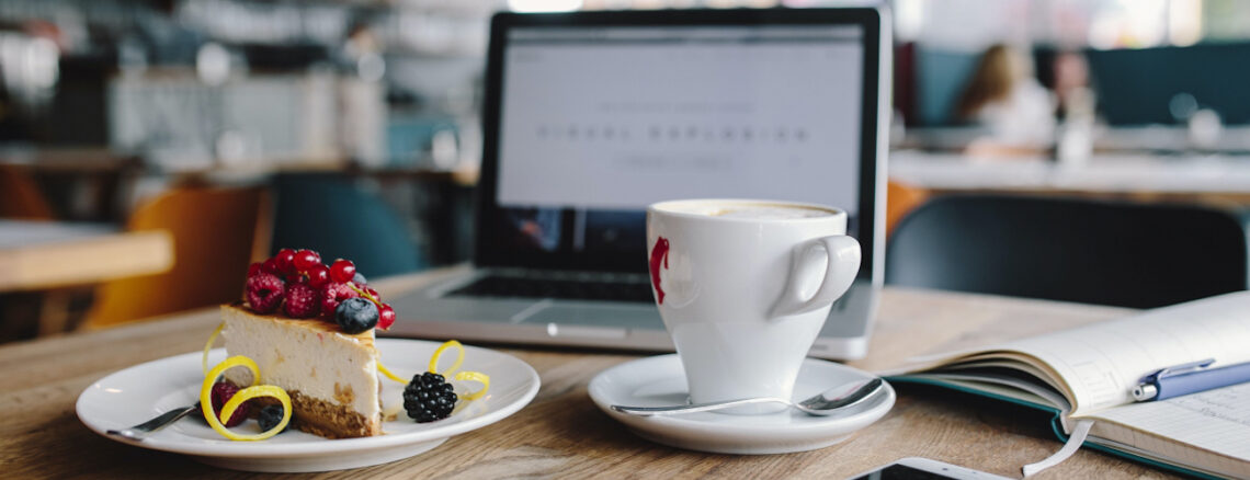 Laptop with coffee cup and piece of cheesecake