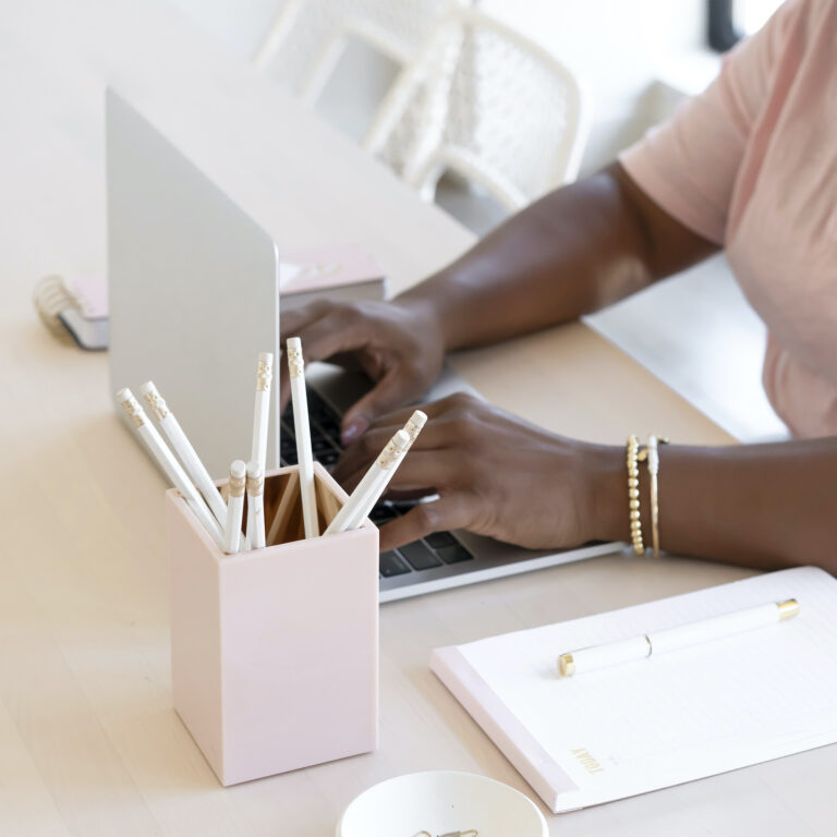 woman typing at her laptop with pencils in a pink pencil holder