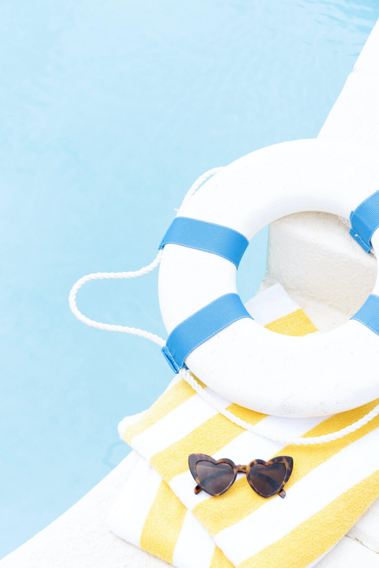 Pool with white and blue float on a yellow and white striped towel