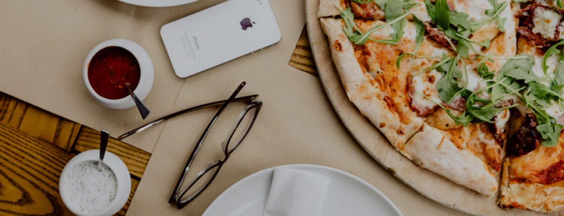 pizza on a table with glasses and a cellphone