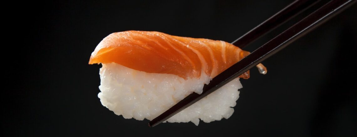 a piece of salmon on top of rice, held with chopsticks