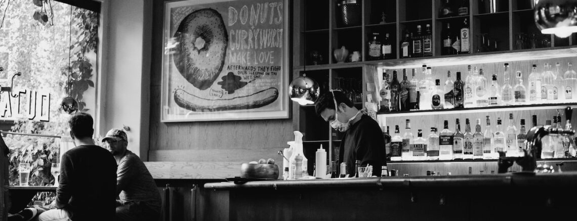bartender with a mask behind a bar in black and white