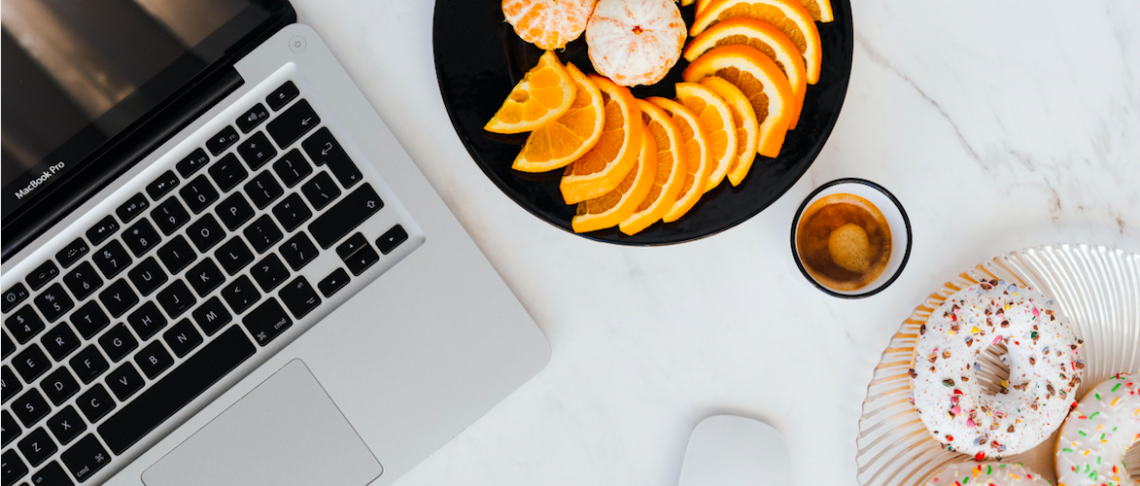 Laptop, oranges, and sprinkled donuts on a white marble table