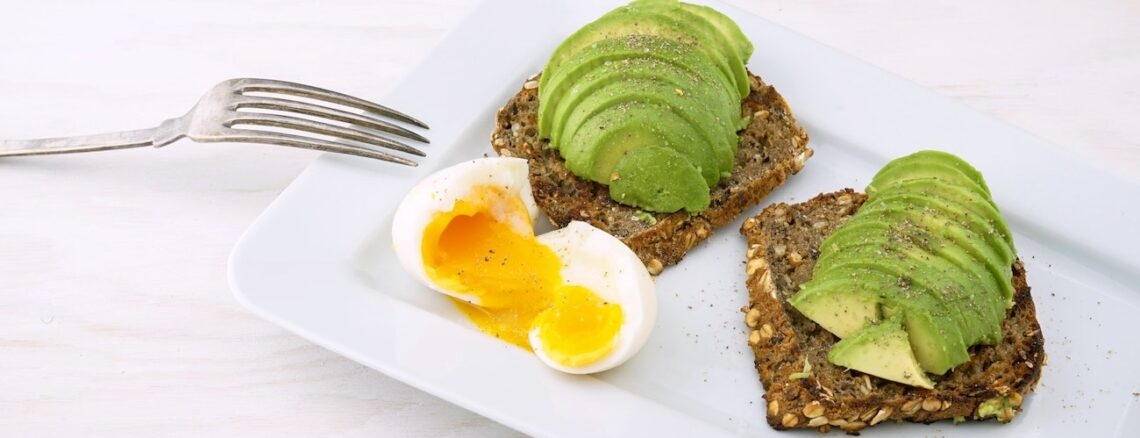 Two slices of whole grain toast with sliced avocado on top and a soft boiled egg