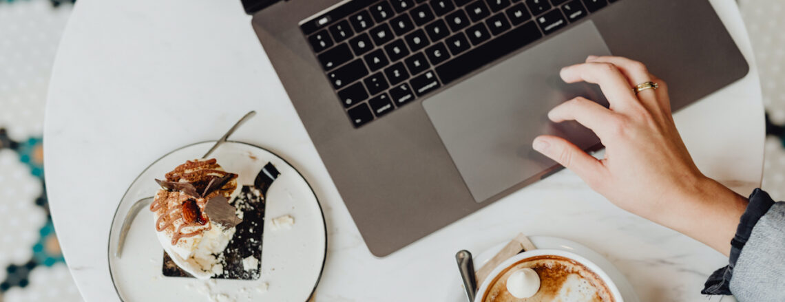 Laptop on white marble table with cup of coffee and cake