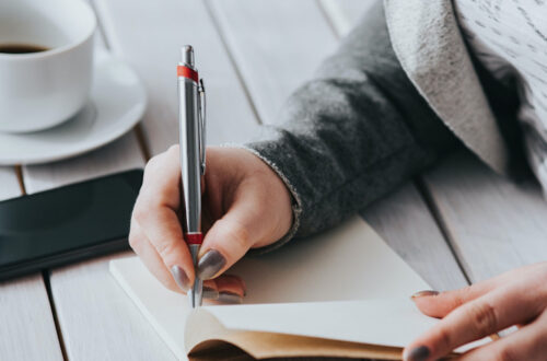Woman in grey sweater writing in a small notebook