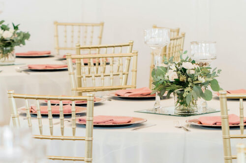 Wedding venue with white linens and gold chiavari chairs