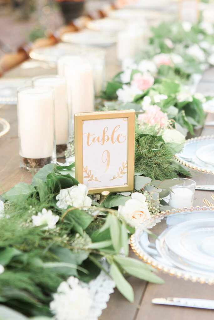 Greenery and white candles with a table number for a wedding venue blog