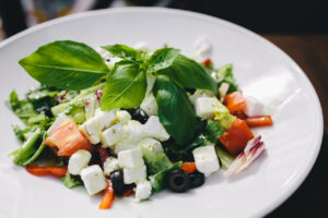 Greek salad of greens black olives, feta, and goat cheese on a white plate