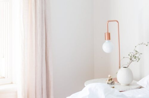 hotel room with white linens and gold bedside lamp - hotel blog