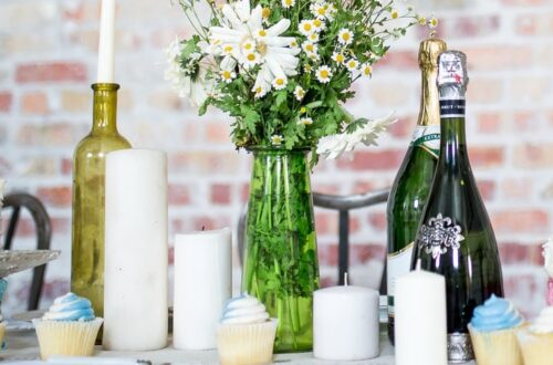 Candles, champagne bottles, cakes and cupcakes on a long white table in front of a brick wall