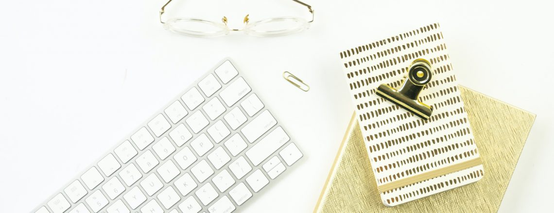 apple keyboard with gold notebooks