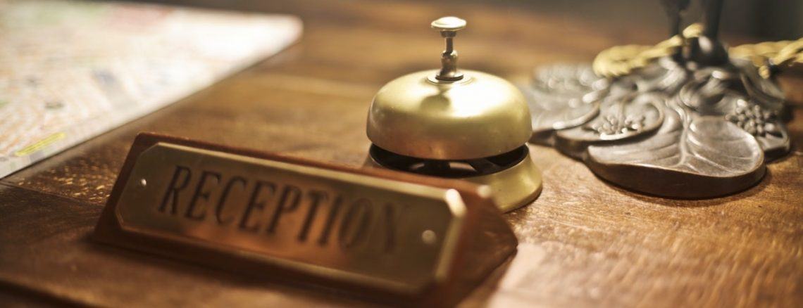"""Hotel desk with brass plaque that says """"reception"""""""